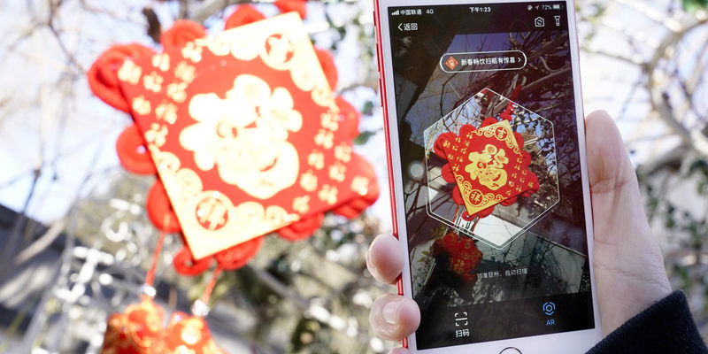 A person using a smartphone to scan a Chinese 'Fu' (blessing) decoration — still from a QQ video