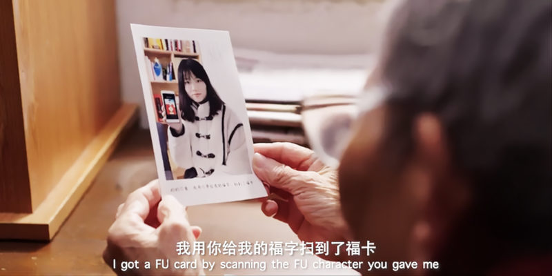 An older person looking at a photograph of a young woman holding up her phone with the 'Fu' character on its screen — still from a QQ video by Qian Chen, Seeeklab